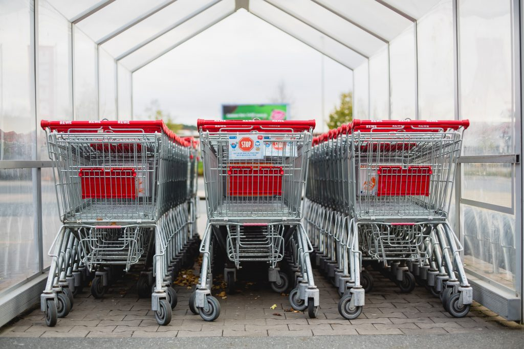 A row of branded trolleys lined up at a trolley bay